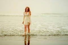 Fille de l'adolescence marchant hors des vagues Photos stock