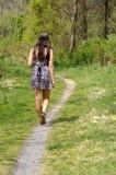 Fille de l'adolescence marchant sur un chemin Image stock