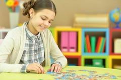 Fille de l'adolescence rassemblant des morceaux de puzzle Photo libre de droits