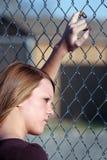 Fille de l'adolescence regardant par la frontière de sécurité Images stock