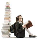 Fille de l'adolescence s'asseyant à une pile de livres Photo stock