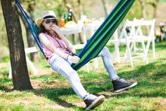 Fille de l'adolescence s'asseyant dans l'hamac sur la r?ception en plein air et mangeant le g?teau photo stock