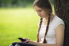 Fille de l'adolescence s'asseyant pr?s de l'arbre avec le t?l?phone portable Images stock