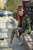 Fille de l'adolescence s'asseyant sur la restriction sur une rue de ville Marche photos libres de droits