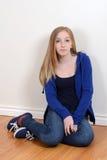 Fille de l'adolescence s'asseyant sur le plancher Image libre de droits