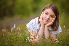 Fille de l'adolescence se trouvant sur l'herbe Photographie stock libre de droits