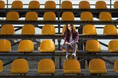 Fille de l'adolescence seule s'asseyant sur des tribunes, Photos libres de droits