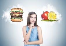 Fille de l'adolescence songeuse dans la robe bleue, choix de nourriture Photos stock