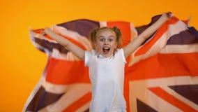 Fille de l'adolescence de sourire sautant avec le drapeau britannique, encourageant pour l'équipe de football nationale banque de vidéos