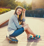 Fille de l'adolescence sur le longboard sur la rue Photo libre de droits