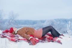 Fille de l'adolescence sur le plaid dans la neige images stock