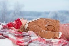 Fille de l'adolescence sur le plaid dans la neige photographie stock libre de droits