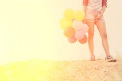 Fille de l'adolescence tenant les ballons colorés sur le sable Photographie stock