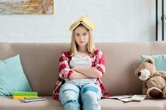fille de l'adolescence triste d'étudiant avec le livre sur la tête se reposant sur le divan à la maison et le regard images libres de droits