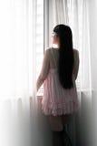 Fille de l'Asie se tenant prêt la fenêtre Image libre de droits
