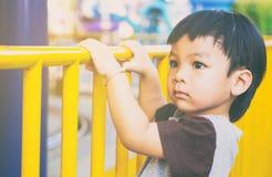 Fille de l'Asie tenant dessus la barrière de rue photographie stock