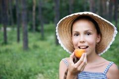 Fille de la préadolescence avec l'abricot Photographie stock libre de droits