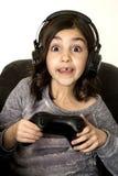 Fille de la préadolescence avec le jeu vidéo jouant grand ouvert de yeux excité Photographie stock libre de droits