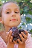 Fille de la préadolescence de sourire avec des raisins Images stock