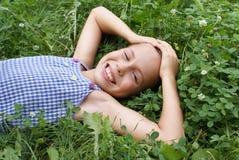 Fille de la préadolescence de sourire sur le trèfle Images stock