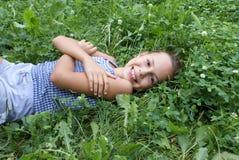 Fille de la préadolescence de sourire sur le trèfle Photo libre de droits