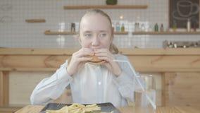 Fille de la préadolescence mangeant l'hamburger avec l'appétit en café banque de vidéos