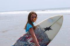 Fille de la préadolescence portant une planche de surfing à l'océan Images libres de droits
