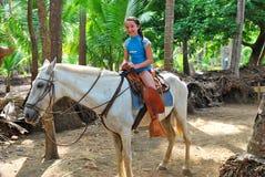 Fille de la préadolescence sur un cheval blanc dans les tropiques Photo stock