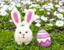 Fille de lapin de Pâques avec l'oeuf de pâques sur des gras verts avec des fleurs dedans Image libre de droits