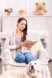 Fille de lecture dans le fauteuil et son chien autour Image stock