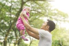 Fille de levage de père avec le fond d'arbre de tache floue Image stock