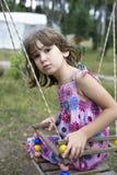 Fille de Litle s'asseyant sur l'oscillation Photographie stock libre de droits