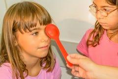 Fille de Littlie passant l'examen d'examen de la vue au bureau d'optométriste images libres de droits