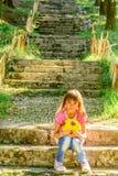 Fille de Littlle s'asseyant sur les escaliers en parc images stock