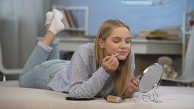 Fille de lycée appliquant son premier lustre rose de lèvre s'admirant, adolescence banque de vidéos