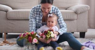 Fille de mère et de bébé arrangeant des fleurs à la maison clips vidéos