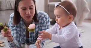 Fille de mère et de bébé arrangeant des fleurs banque de vidéos