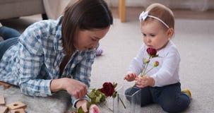 Fille de mère et de bébé insérant les fleurs roses dans le vase clips vidéos
