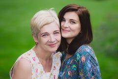 Fille de mère et d'adulte en parc vert posant ensemble Photos libres de droits