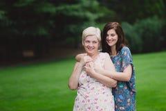 Fille de mère et d'adulte en parc vert posant ensemble Photos stock