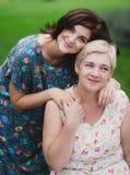 Fille de mère et d'adulte en parc vert posant ensemble Image libre de droits