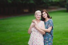 Fille de mère et d'adulte en parc vert posant ensemble Image stock