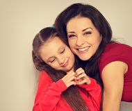 Fille de mère et d'enfant étreignant avec les visages émotifs heureux et montrant le signe de coeur closeup images stock