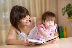 Fille de mère et d'enfant lisant un livre Photographie stock