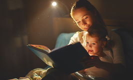 Fille de mère et d'enfant lisant un livre dans le lit Images stock