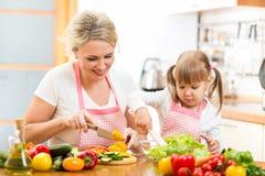 Fille de mère et d'enfant préparant la nourriture saine Photographie stock libre de droits