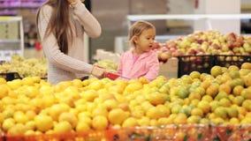 Fille de mère et de bébé en fruits et légumes de achat de supermarché clips vidéos