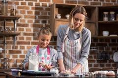 fille de mère et de préadolescent dans les tabliers faisant des biscuits ensemble photos stock