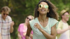 Fille de métis dans des lunettes de soleil jaunes dansant au bâti d'exposition de talent, jeunesse banque de vidéos