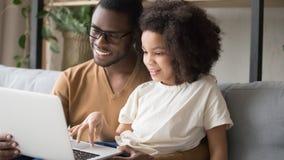 Fille de métis et père africain ayant l'ordinateur portable d'utilisation d'amusement images stock
